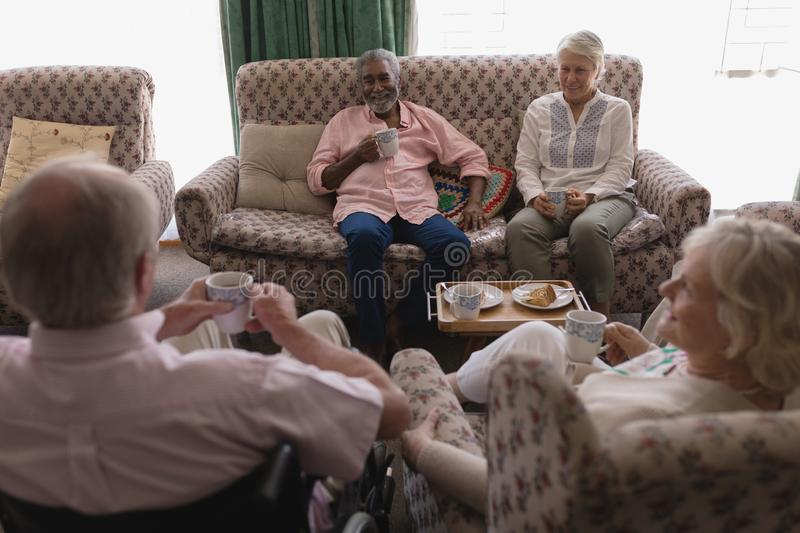 Senior couples interacting with each other while having coffee in living room royalty free stock photography