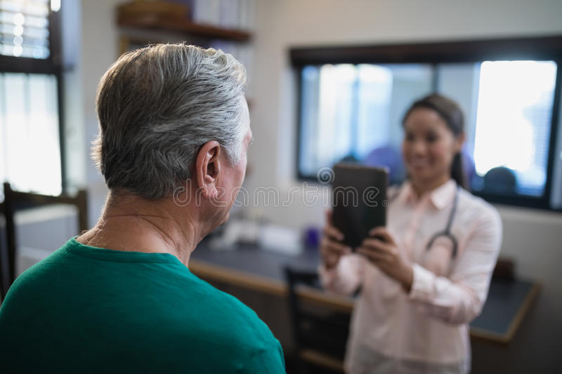 Rear view of senior male patient being photographed by female therapist stock photo