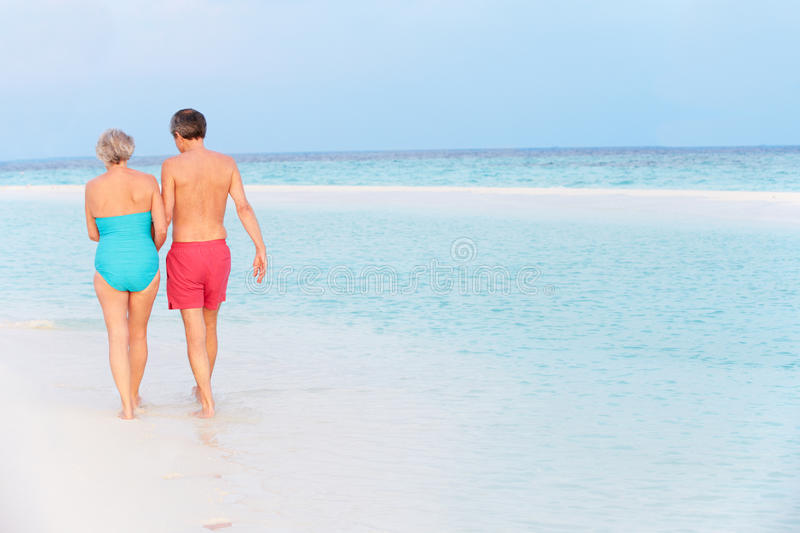 Rear View Of Senior Romantic Couple Walking In Tropical Sea stock photography