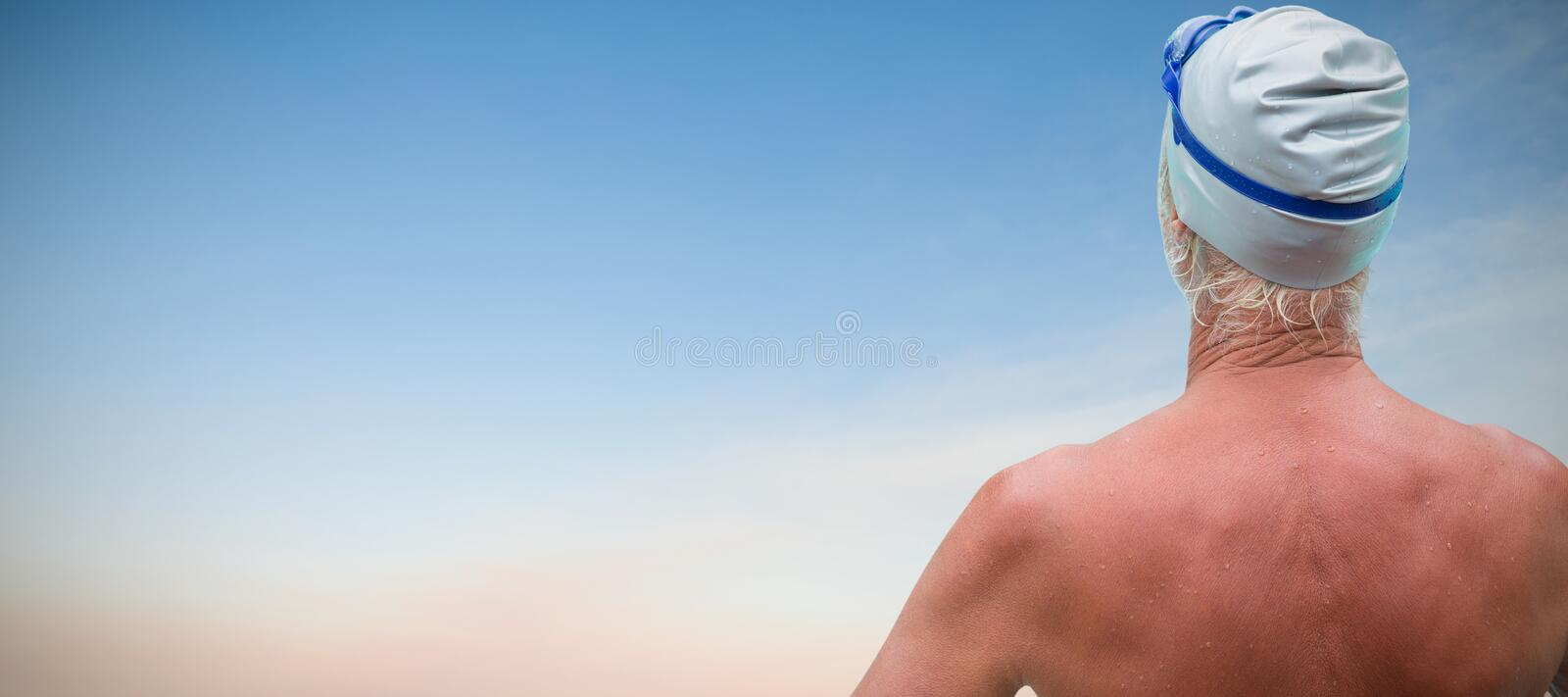Composite image of rear view of senior swimmer. Rear view of senior swimmer against beautiful sunset on a sunny day stock photography