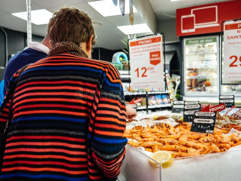 Rear view senior woman buying shrimps supermarket royalty free stock photos