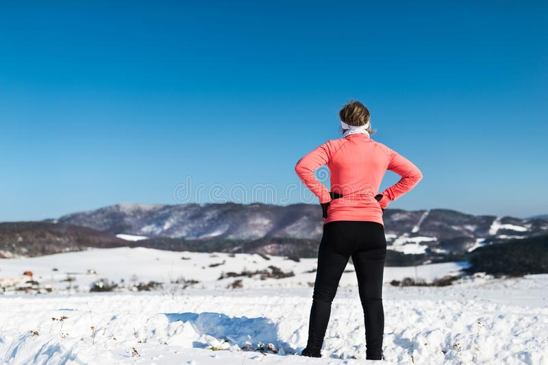 Rear view of senior woman runner resting in winter nature. royalty free stock photos