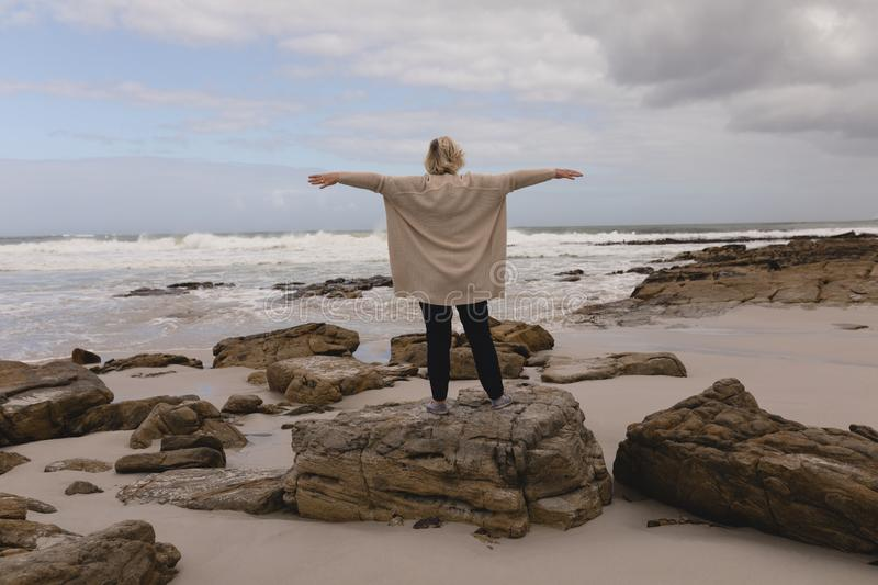 Senior woman standing with arms outstretched on the rock at beach royalty free stock photo