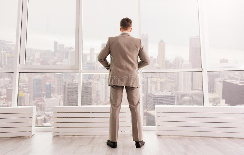 Rear view of serious businessman standing in the office royalty free stock photography