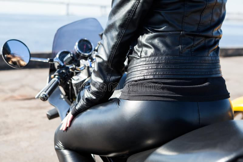 Rear view at sexy woman sitting on motorcycle in black leather pants, ass with back view royalty free stock photos