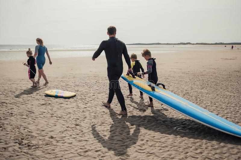 Family Surfing at the Beach. Rear view shot of a family walking down to the seaside to go surfing stock image