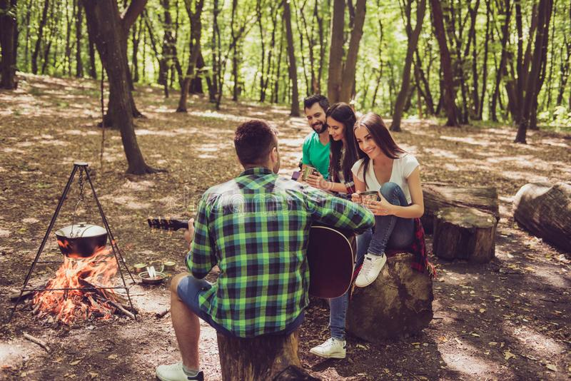 Rear view shot of guy playing guitar in the wood near fire. Three friends are sitting near, smiling, enjoying. Dinner is cooking stock photos
