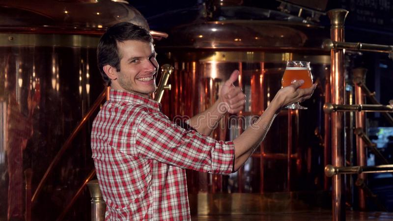 Rear view shot of a happy brewer showing thumbs up after examining beer stock image