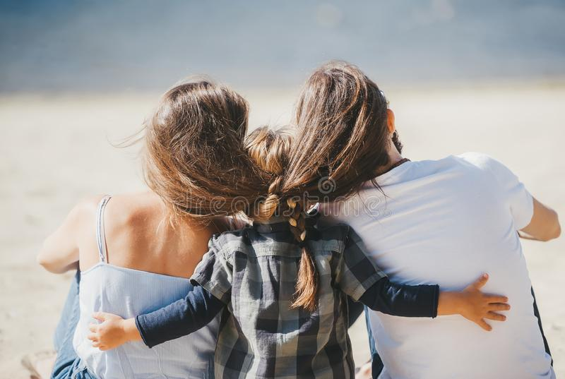 Rear view shot of happy family enjoying the weekend, sitting on sand on a beach stock photo
