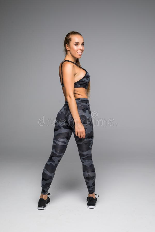 Rear view shot of a healthy young woman in sportswear. Full length image of muscular female model standing looking away at copyspa stock photography