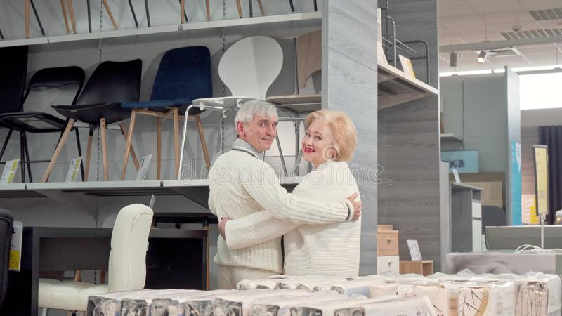 Rear view shot of a lovely senior couple choosing furniture together at the store. Rear view shot of a senior couple choosing furniture together at the store royalty free stock image