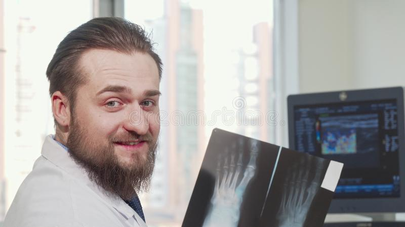 Rear view shot of a male doctor looking at foot x-ray of a patient stock photography