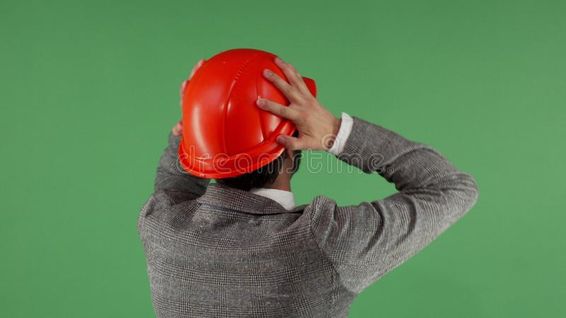 Disappointed engineer rubbing his neck. Rear view shot of a professional architect looking at the green chromakey screen rubbing his neck disappointed. Male royalty free stock photos
