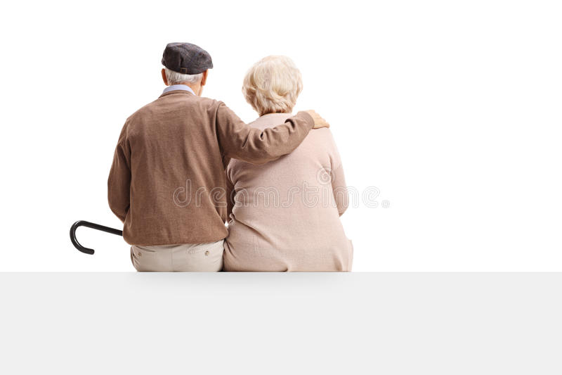 Rear view shot of senior couple sitting on panel royalty free stock photo
