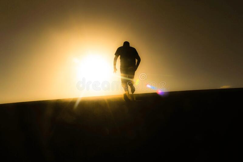 Rear View of Silhouette Man Against Sky during Sunset royalty free stock photography