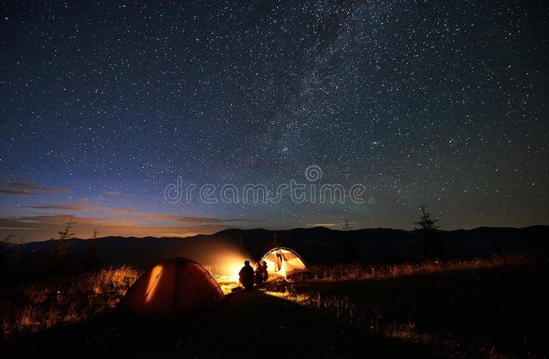 Mother and two sons hikers at camping in mountains under night sky full of stars and Milky way. Rear view of silhouette mother and two sons hikers at camping in royalty free stock photos