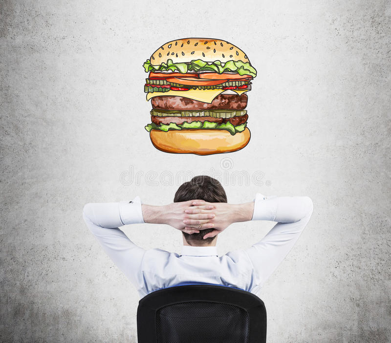 A rear view of sitting relaxing man who is dreaming about burger. A fast food concept. Concrete background stock image