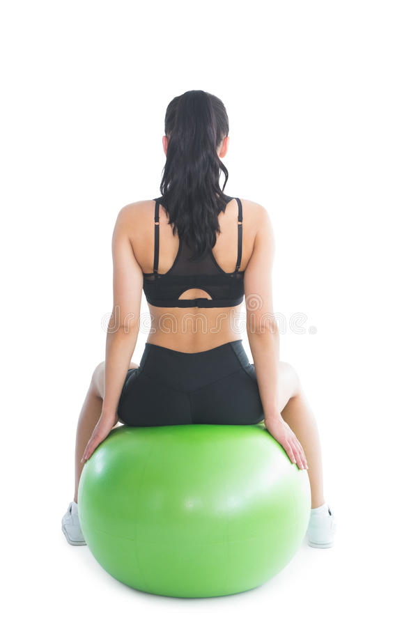 Rear view of slender ponytailed woman sitting on an exercise ball stock images
