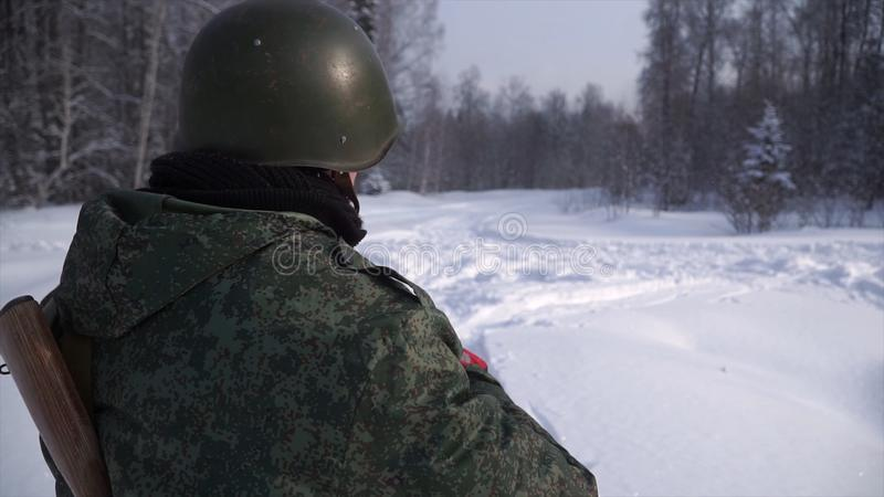Rear view of the soldier in the forest in winter. Clip. The soldier stands at his post guarding him. Military protection royalty free stock photo