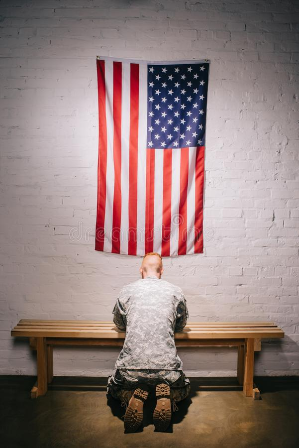 Rear view of soldier in military uniform praying with american flag on white brick wall, americas independence. Day concept stock photo