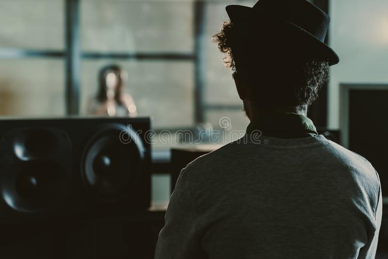 Rear view of sound producer looking at singer recording song behind glass. At studio stock photography