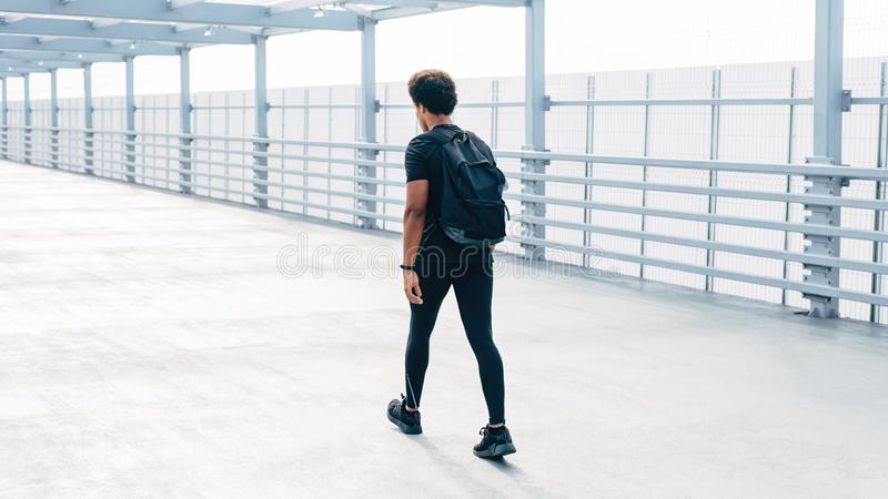 Rear view of a sportsman walking with backpack stock photos