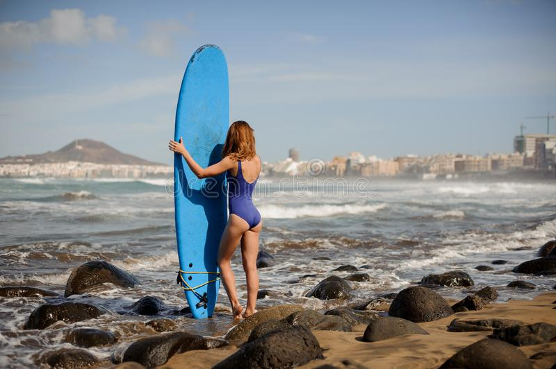 Rear view of a sporty girl in the blue swimsuit standing with the surf stock image