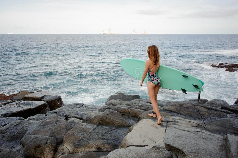 Rear view sporty girl in the multi colored swimsuit walking with the surf on the rocks on the beach royalty free stock photos