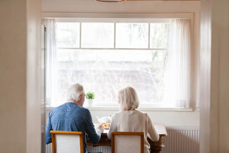 Rear view spouses sitting on chairs at dining table. Rear back view pensioner spouses sitting on chairs at dining table near window in modern kitchen at home stock images
