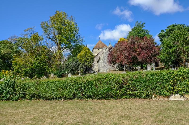 Rear view of St. Andrews church in the Sussex village of Jevington. Shot is taken on a bright blue sky morning and shows the royalty free stock image