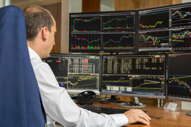 Rear view of stock trader analyzing data at multiple computer screens. stock photos