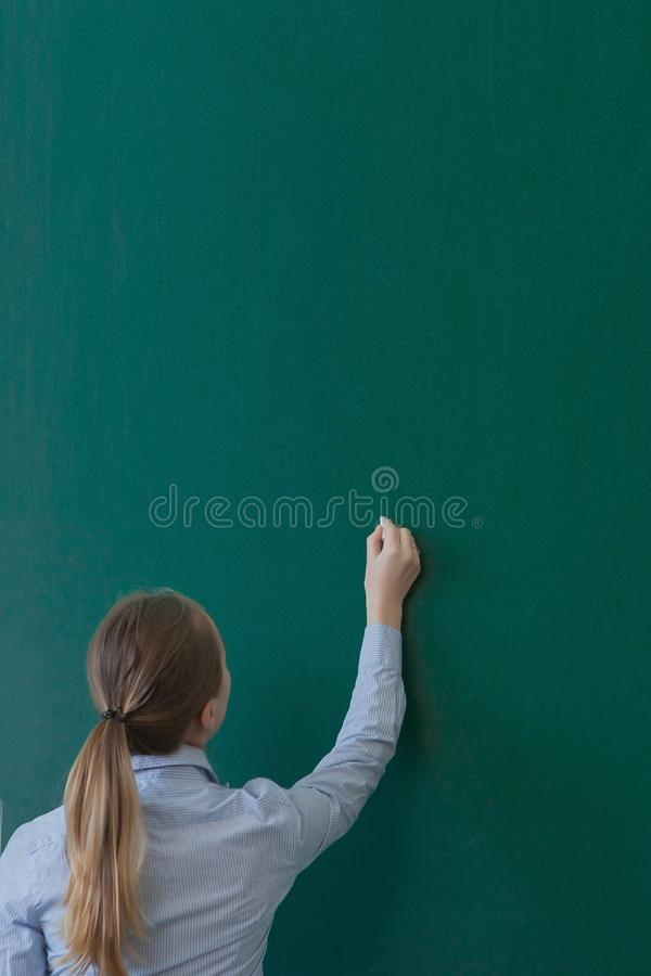 Rear view of a student or teacher with long brunette hair writing on a blank green blackboard or chalkboard with copyspace royalty free stock images