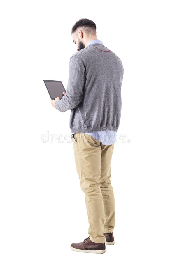 Rear view of stylish bearded businessman using tablet pad computer. Full body length portrait isolated on white studio background royalty free stock images
