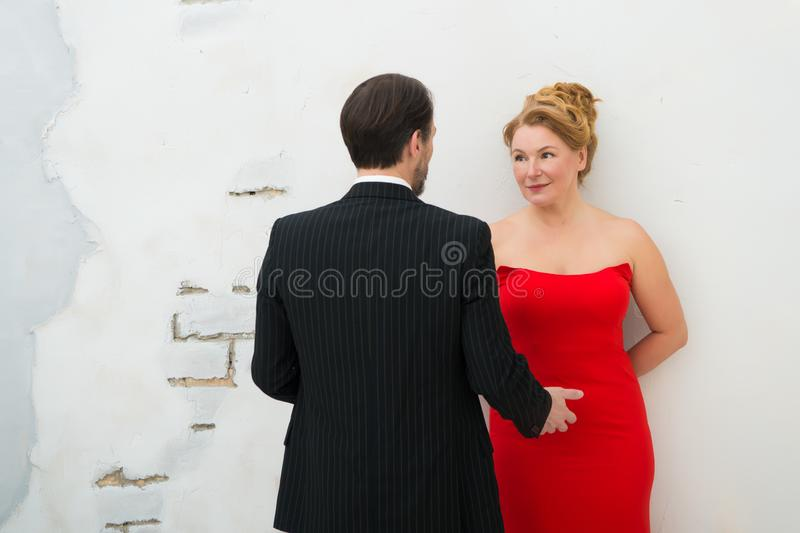 Rear view of stylish man in striped suit talking to his charming wife royalty free stock photography