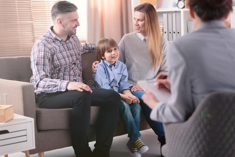 Rear view at successful female psychotherapist helping young family with a child to solve problems in relationship. Happy family stock photography