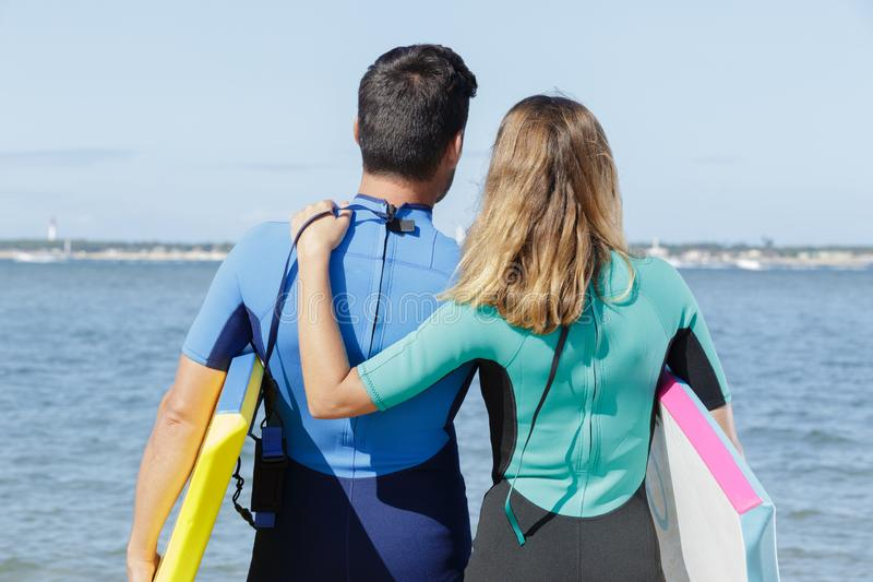 Rear view surfing couple looking out to sea stock photography