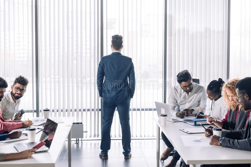 Multiracial business coworkers talking, interacting on workplaces. Rear view of tall caucasian HR professional in formal suit waiting the young beginners, being royalty free stock images