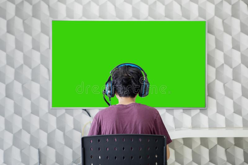 Rear view of teen boy playing video games royalty free stock image