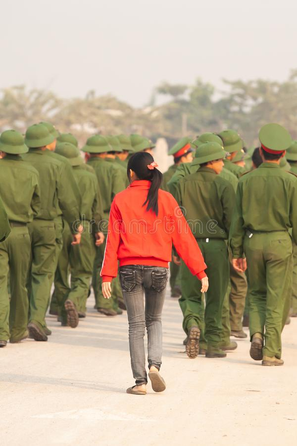 Rear view, Teen girl in red shirt walking with a group of Young Vietnamese soldier on the street, during site visit program. Dien. Rear view, Teen girl in red royalty free stock photo