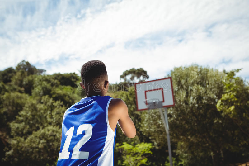 Rear view of teenage boy practicing basketball. Rear view of male teenage boy practicing basketball in court on sunny day stock photo