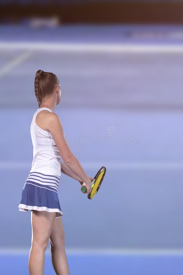 Rear view of tennis player serving during a match royalty free stock image