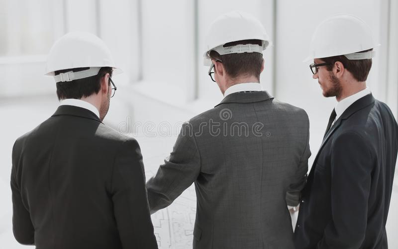 Rear view.three architect designer discussing the new designs stock photo