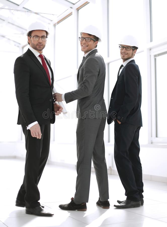 Rear view.three architects standing in the corridor of the new building royalty free stock photo