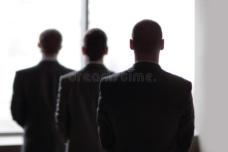 Rear view of three businessmen as they stare at the big window overlooking the city royalty free stock image