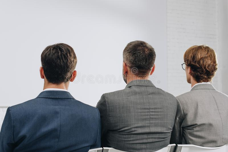 rear view of three businessmen sitting on chairs during training stock image