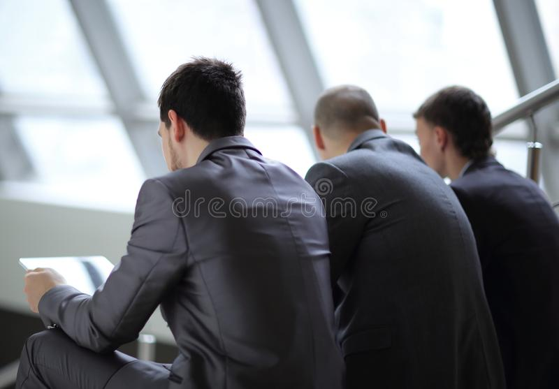 Rear view.three employees with a tablet sitting in the hallway office stock images