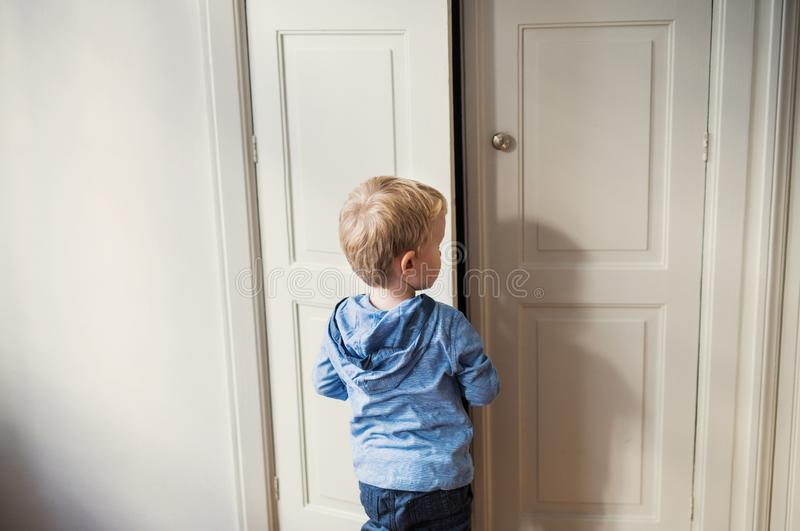 A rear view of toddler boy standing near door inside in a bedroom. A rear view of toddler boy standing near wardrobe door inside in a bedroom. Copy space royalty free stock photography