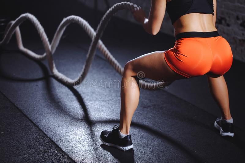 Rear view of tonned woman training with battle rope in cross fit gym. Close up back view of tonned woman training with battle rope in cross fit gym royalty free stock photos