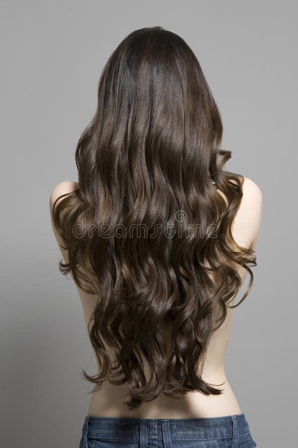Rear View Of Topless Woman With Long Wavy Hair. Rear view of a topless woman with long brown wavy hair against gray background royalty free stock photography