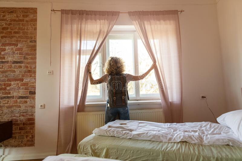 Tourist in the hotel room pulling the curtains to see the view stock photos